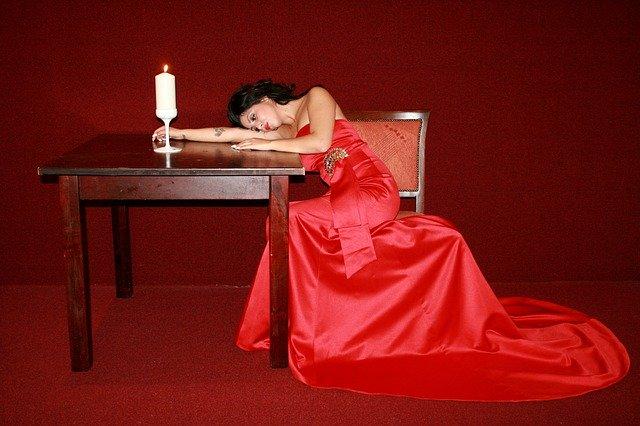 Žena v červených dlouhých šatech s vlečkou, sedící u stolu se zapálenou svící