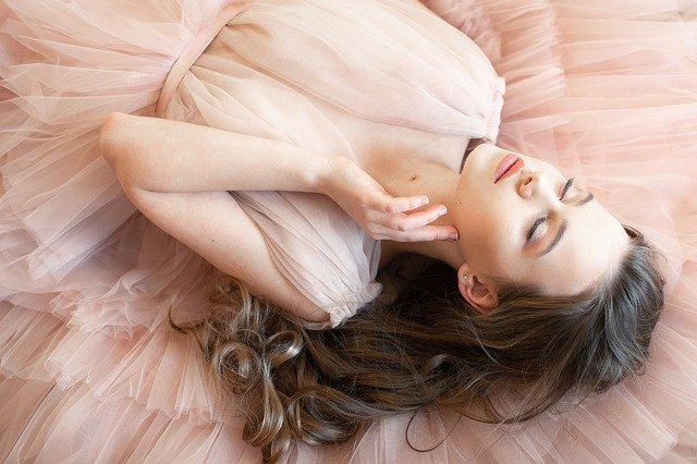 Ležící dívka v záplavě růžových nadýchaných šatů