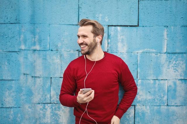 Usmívající se muž držící mobil se sluchátky na uších