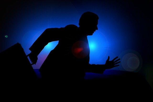 běžící kancelářský muž na modrém pozadí ve tmě