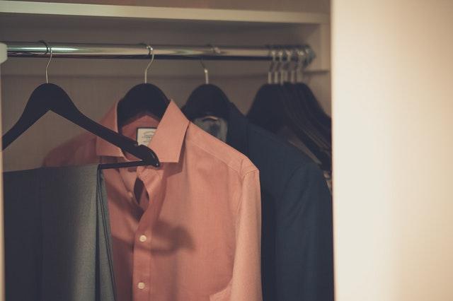 Oblečení na ramínkách ve skříni