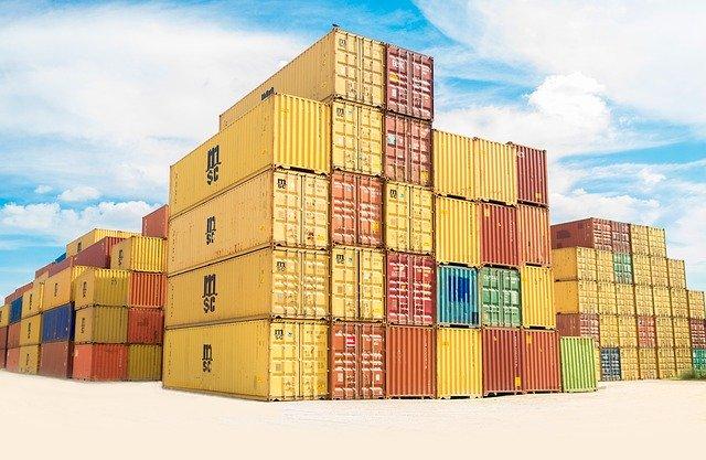 kontejnery naskládané na sobě, velké žluté na volné ploše, vzadu modrá obloha s bílými mráčky