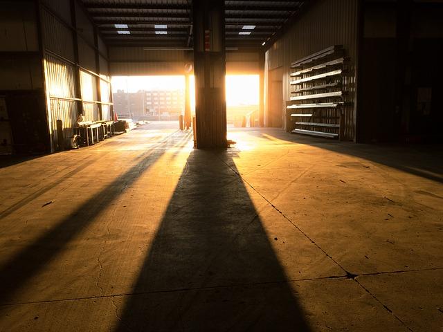 velké prázdné skladiště, otevřená vrata, východ slunce, jak svítí do prostoru