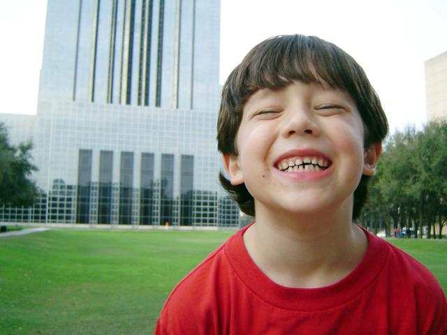 šťastný chlapec v červeném tričku na předměstí