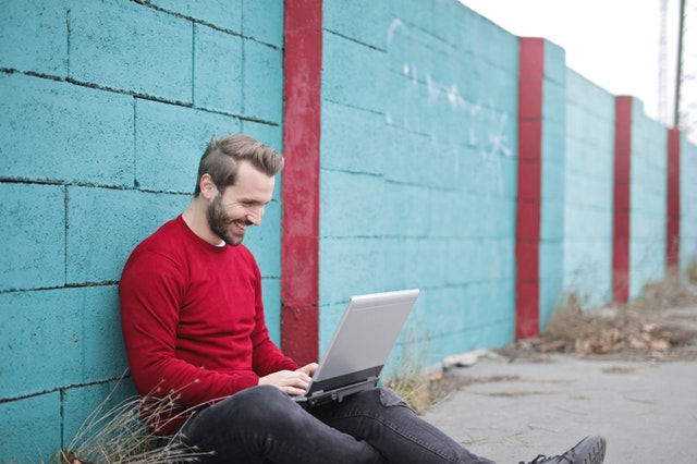 modrý betonový plot, muž s počítačem